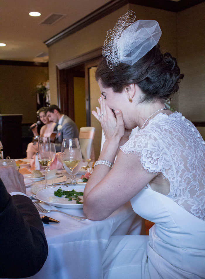 Bride crying tears of joy with bridesmaid singing
