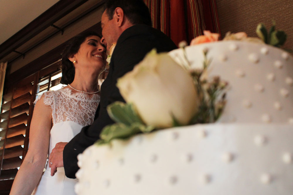 bride and groom looking into each others eyes about to cut the cake