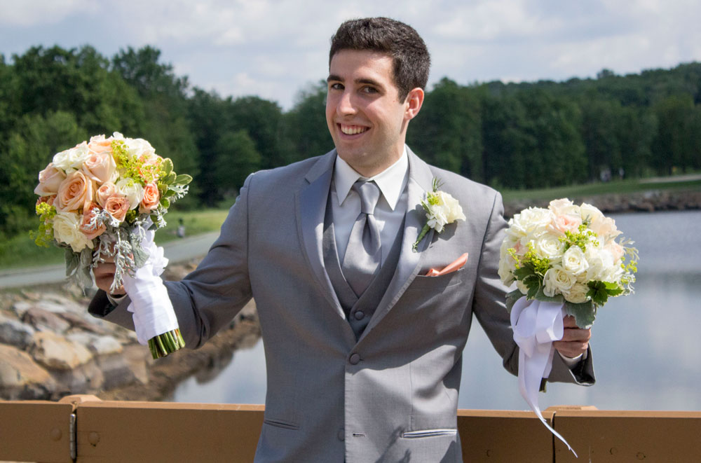Groomsmen holding 2 bouquets of flowers