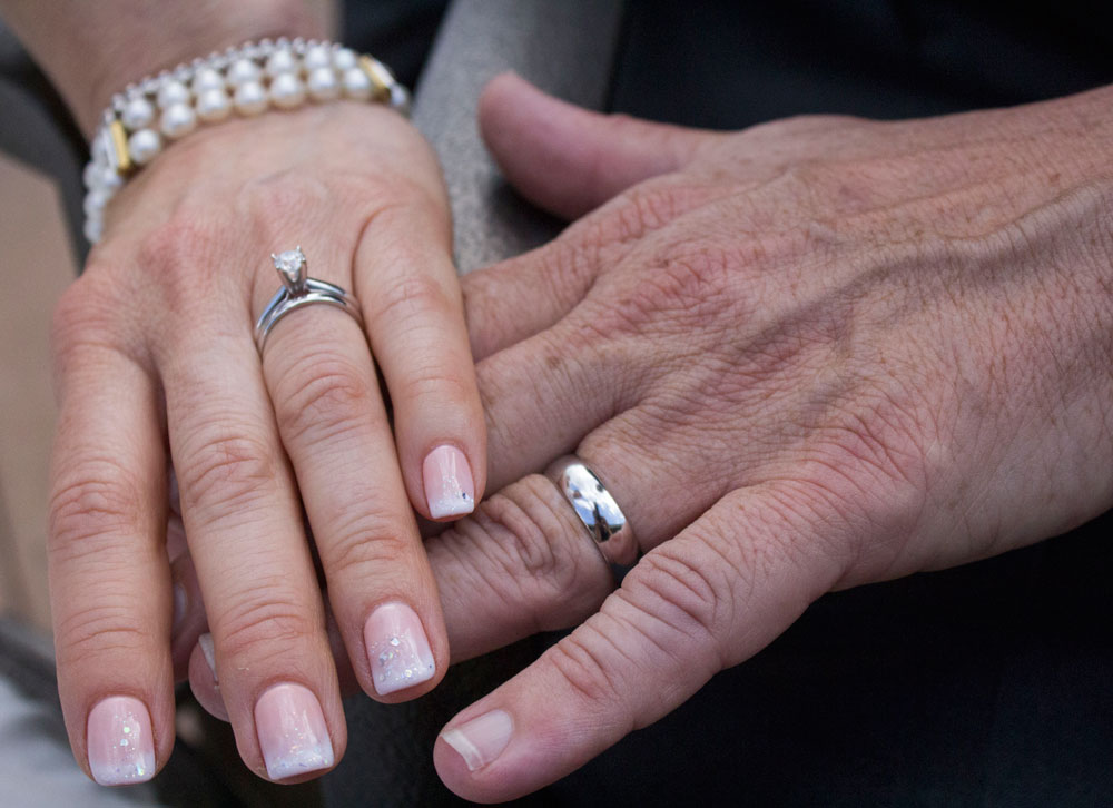 hands joined together with wedding rings on