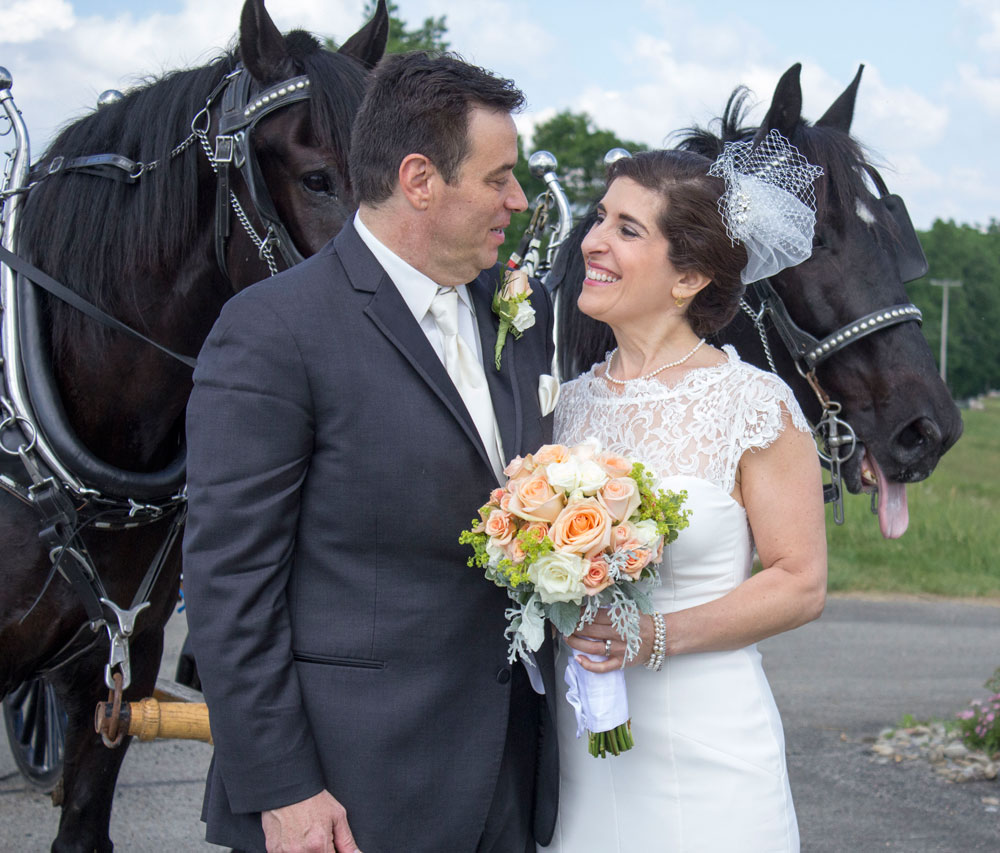 bride and groom with horses in carriage behind them